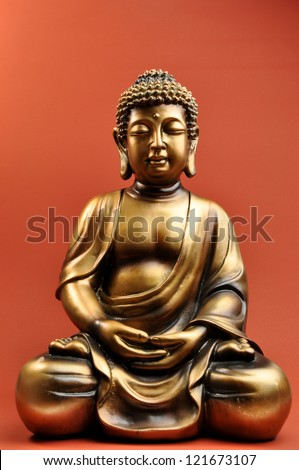 Beautiful Buddha statue with eyes closed against a red orange background evokes a feeling of peace, calm and tranquility. For Zen style interior decor or Buddhist artifact. - stock photo