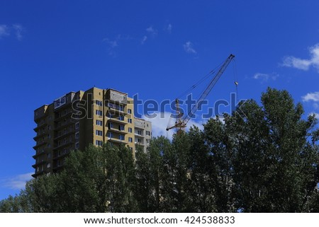 beautiful building and a successful business  build tall buildings for residents. standing next to a construction crane. blue sky - stock photo