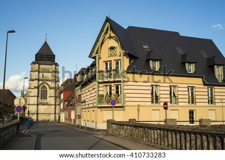 Beautiful building and the church tower in Pont-l'Eveque (Calvados, Normandy, France). - stock photo