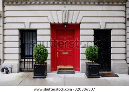Beautiful building. Entrance red door, Manhattan New York, USA. Classic apartment estate in New York City. Beautiful view of midtown property, NYC. Business and finance, luxury life background. - stock photo