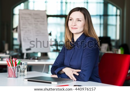 Beautiful Business Lady in official clothing black Jacket and white Shirt sitting at grey Table with Computer Flower and other Business Lifestyle Items smiling Face satisfied with good Job well done - stock photo