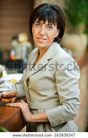 Beautiful business woman holding glass of wine at corporate events. - stock photo