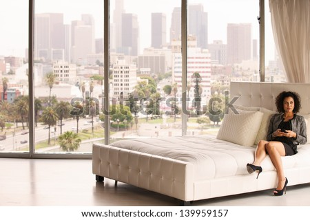 Beautiful Business Woman in a Penthouse Suite at a Hotel on her cell phone - stock photo