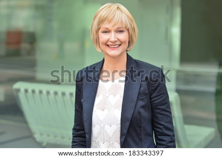 Beautiful business woman in front of glass window - stock photo