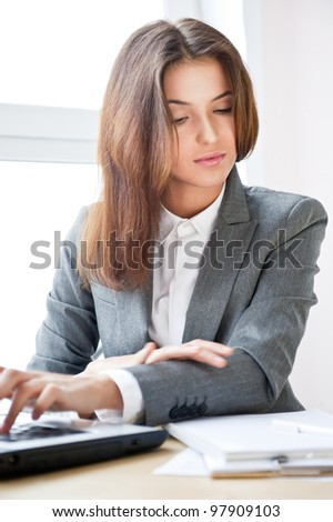 Beautiful business woman looking at papers while working on computer at her office - stock photo