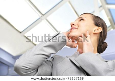 beautiful business woman on the phone at modern building against glass roof - stock photo