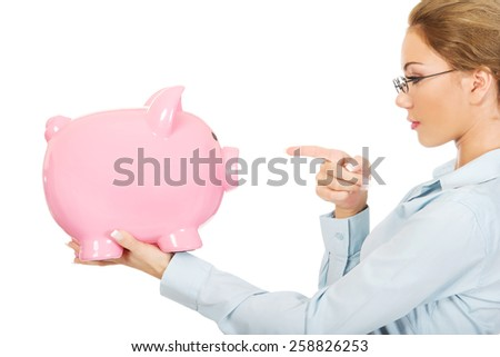 Beautiful business woman pointing on piggy bank. - stock photo