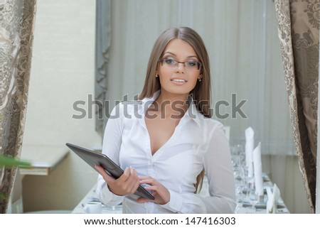 Beautiful business woman posing with tablet PC - stock photo