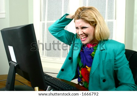 Beautiful business woman pulling her hair, in desperation, while looking at her office computer. - stock photo