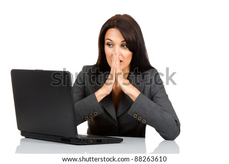 beautiful business woman scared, terrified sitting at the desk working using laptop looking at screen, isolated over white background, computer problem concept - stock photo