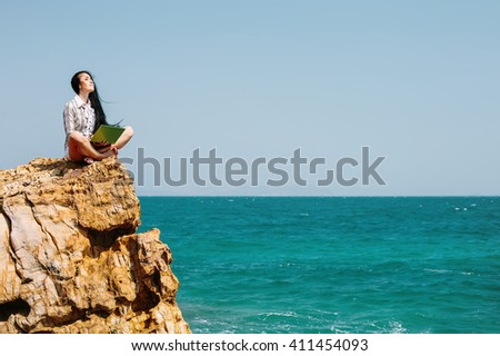 Beautiful business woman sitting on stone cliff on blue sea beach, enjoy freedom, using laptop computer - stock photo