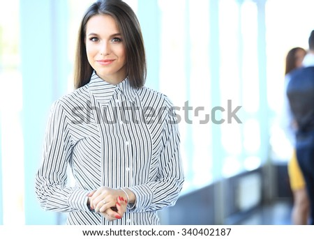 Beautiful business woman smiling and looking at camera in a modern office - stock photo