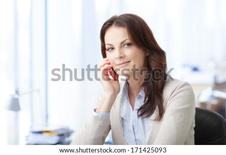Beautiful business woman talking on mobile phone - stock photo