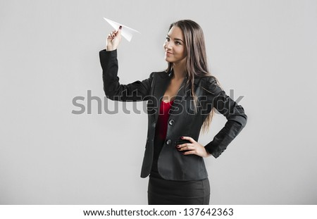 Beautiful business woman throwing a paper plane, over a gray background - stock photo