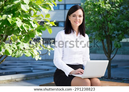 beautiful business woman using laptop in city park - stock photo