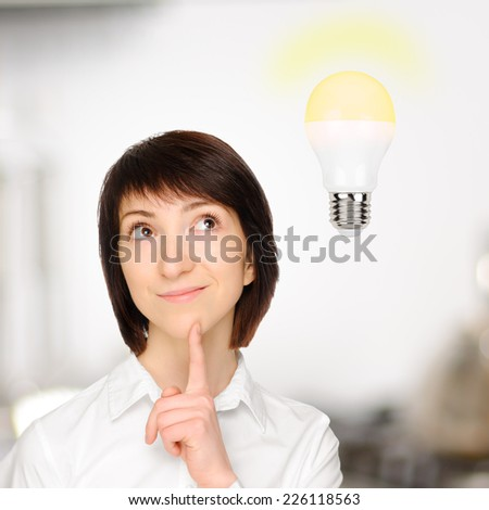 Beautiful business woman with idea light bulb above. - stock photo