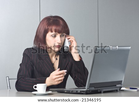 Beautiful businesswoman behind a desktop and a laptop speaks on the phone - stock photo