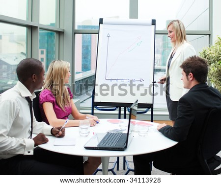 Beautiful businesswoman giving a presentation to her team - stock photo