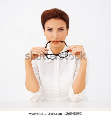 Beautiful businesswoman holding a pair of glasses in her hands as she looks at the camera with a serious expression on a white background - stock photo
