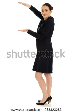 Beautiful businesswoman holding copyspace in hands. - stock photo