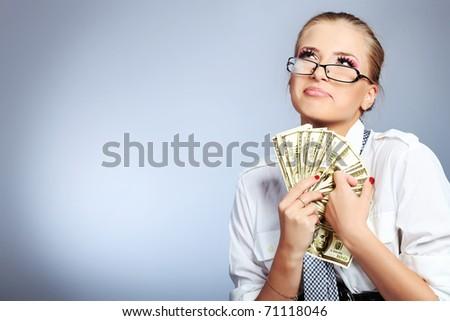 Beautiful businesswoman holding money. Studio shot over grey background. - stock photo