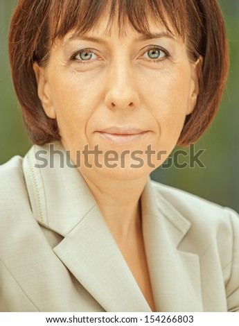 Beautiful businesswoman in bright suit, close-up. - stock photo
