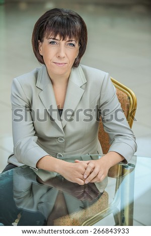 Beautiful businesswoman in bright suit sitting at glass table. - stock photo