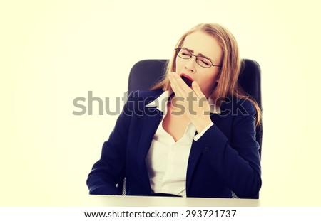 Beautiful businesswoman in glasses yawning - stock photo