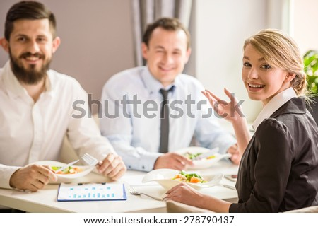 Beautiful businesswoman in suit talking with partners at business lunch. - stock photo
