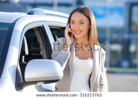 Beautiful businesswoman is talking on the mobile phone and smiling. She is standing near her car and looking forward with joy - stock photo