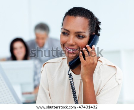 Beautiful businesswoman on phone at her desk - stock photo