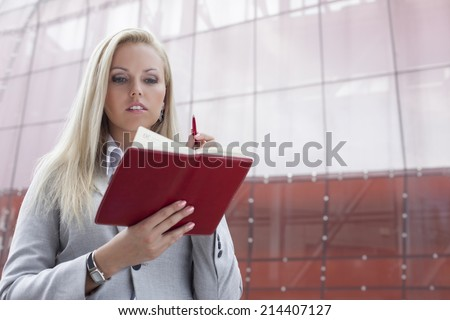 Beautiful businesswoman reading notes in organizer while standing against office building - stock photo