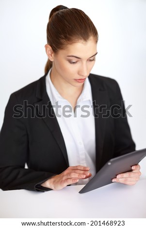 Beautiful businesswoman sitting at table in office and working at tablet pc - stock photo