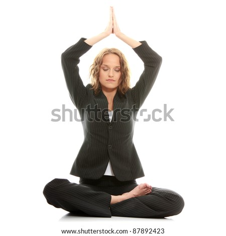 Beautiful businesswoman sitting on white desk in lotus flower position of yoga. Isolated on white - stock photo