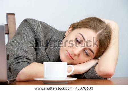 Beautiful businesswoman sleeping at her desk - stock photo