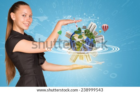 Beautiful businesswoman smiling and looking at camera. Beside is miniature Earth with trees, industrial and residential buildings, air balloons, airplane and surrounded by rings. Network with people - stock photo