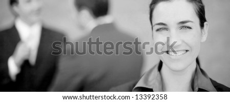 beautiful businesswoman standing and smiling while two businessmen talk in the background - stock photo