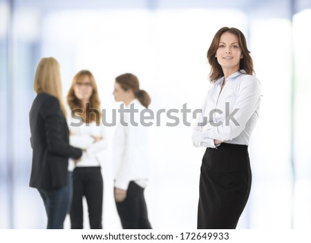 Beautiful businesswoman standing, people in  the background. - stock photo