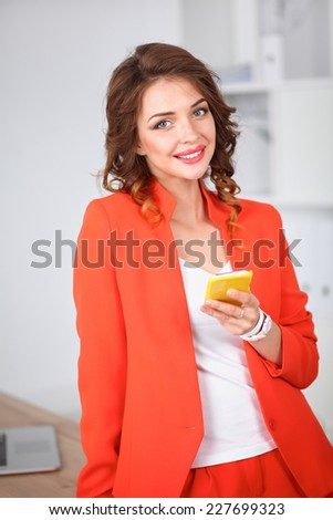 Beautiful businesswoman using cell phone standing in office, isolated - stock photo