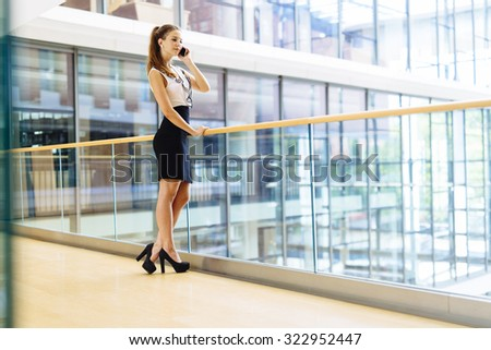 Beautiful businesswoman using phone and smiling - stock photo