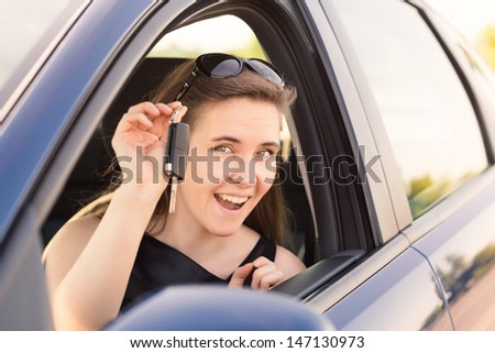 Beautiful businesswoman with carkey in her car - stock photo
