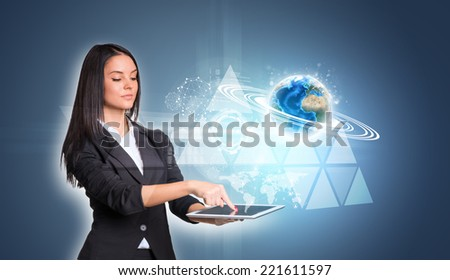 Beautiful businesswomen in suit using digital tablet. Earth with triangles and network. Element of this image furnished by NASA - stock photo