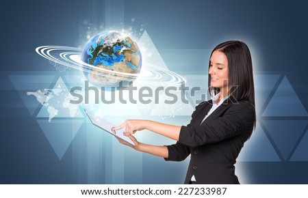 Beautiful businesswomen in suit using digital tablet. Earth with triangles, network and world map. Element of this image furnished by NASA - stock photo