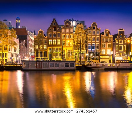 Beautiful calm night view of Amsterdam city. Night time illuminations of buildings with reflections on water and boats in the canal. - stock photo