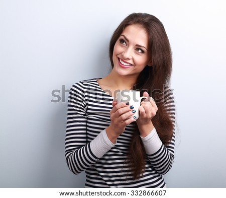 Beautiful calm thinking woman drinking coffee from cup on blue background - stock photo