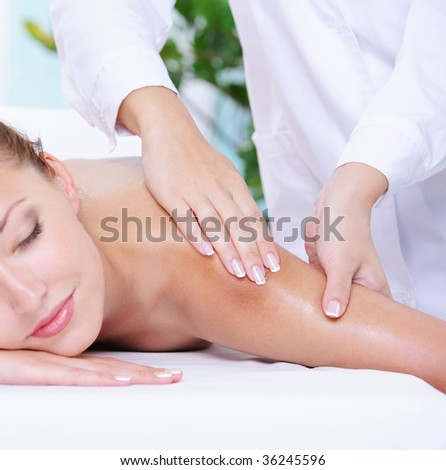Beautiful calm woman getting massage of shoulder in the beauty salon - stock photo