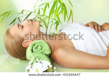 Beautiful calm woman with closed eyes lying down on the massage table and enjoying spa procedures, alternative medicine, healthy lifestyle - stock photo