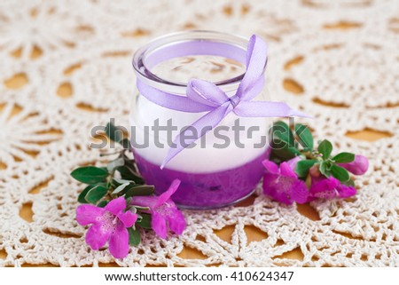 Beautiful candle and pink flowers on cloth background. - stock photo