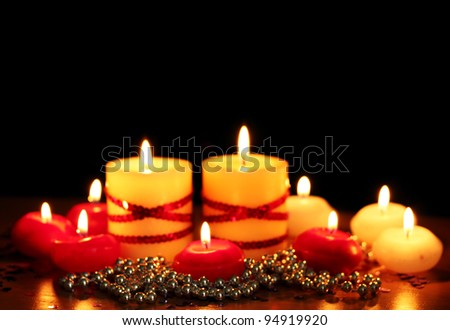 Beautiful candles and decor on wooden table on black background - stock photo