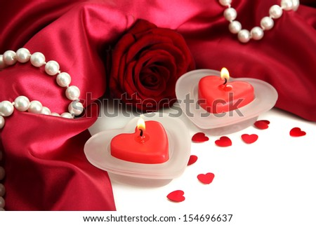 Beautiful candles and rose on red silk background  - stock photo